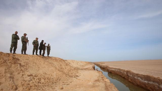 Soldaten stehen in der Wüste auf einem Sandwall, vor ihnen liegt ein Graben gefüllt mit Wasser.