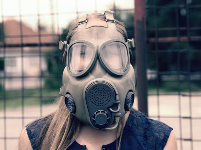 Frau posiert mit Gasmaske