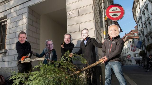Fünf Personen mit Pappmasken der Luzerner Regierungsräte posieren mit einer abgesägten Tanne und einer Motorsäge.