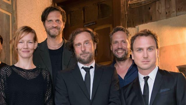Vier Männer und eine Frau haben sich für ein Foto aufgestellt. Sie lächeln in die Kamera.