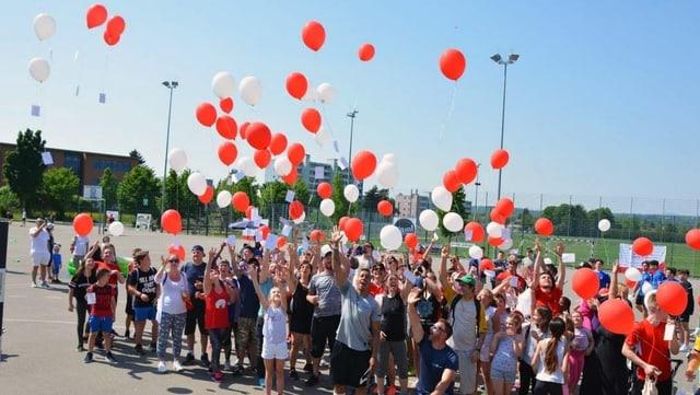 Menschen in Turnklamotten lassen Ballone steigen und feiern, im Hintergrund Wohnblöcke