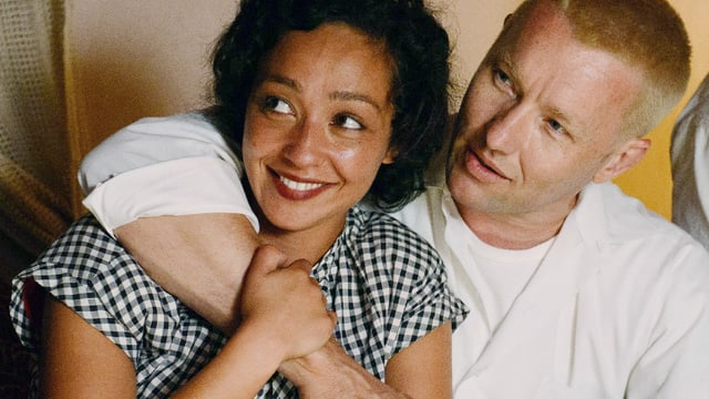 Eine schwarze Frau und ein weisser Mann sitzen in vertrauter Nähe zusammen.