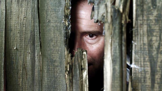 Schauspieler Stefan Kurt schaut durch ein Loch in einer Holzwand