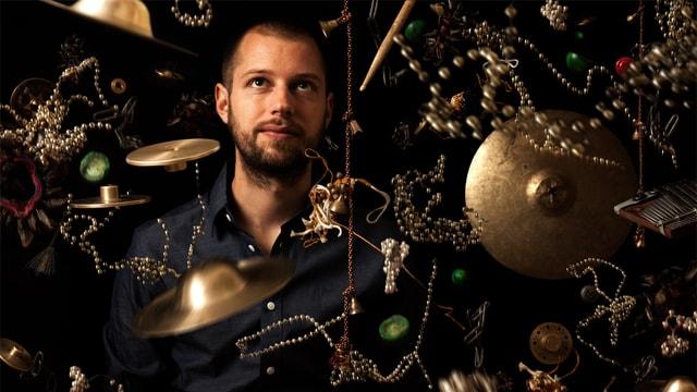 Julian Sartorius blickt durch eine Vielzahl von in der Luft schwebenden Klangkörpern.