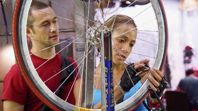 Ein Mann und eine Frau reparieren einen Fahrradreifen.