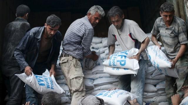 Männer laden Mehlsäcke von einem Hilfskonvoi ab