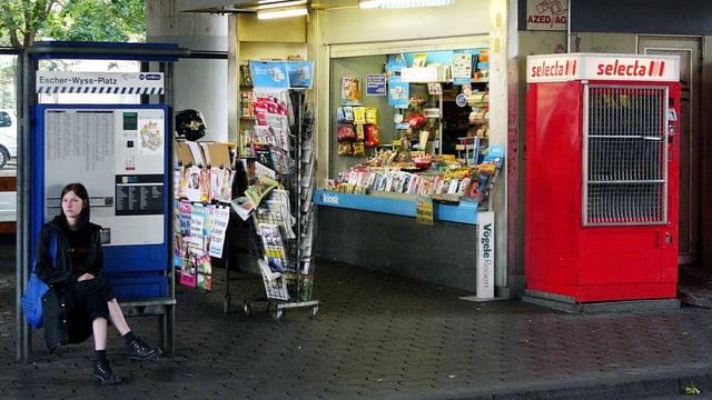 Eine junge Frau sitzt vor einem Schweizer Kiosk. Daneben ist ein roter Selecta-Automat.