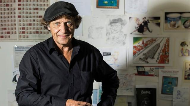 Der Karikaturist Raymond Burki posiert vor seinen Zeichnungen.