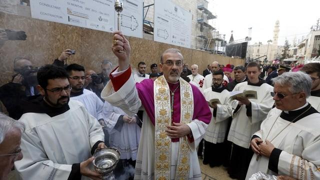 Der Erzbischof segnet mit Weihwasser.
