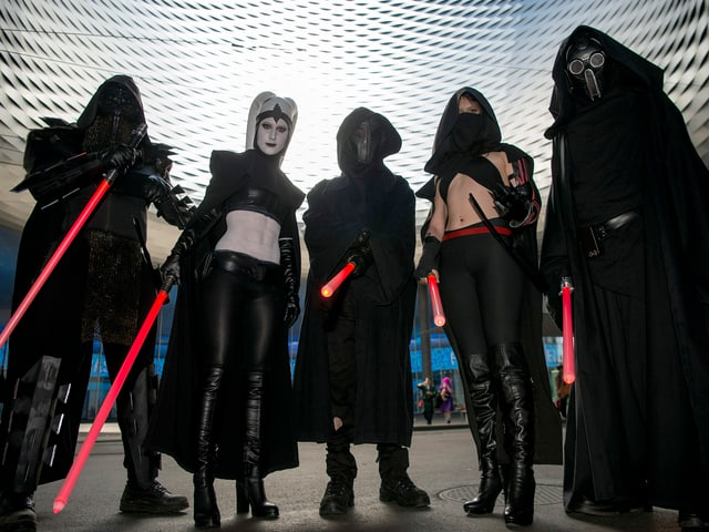 Eine Gruppe von dunkel kostümierten Männern und Frauen. Sie halten Leuchtstäbe in der Hand.