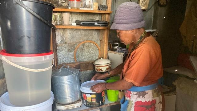 Eine ältere Frau werkelt in einer behelfsmässigen Küche.