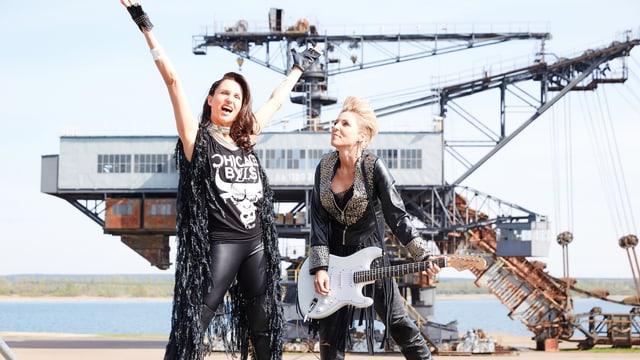 Zwei Damen in Lederoutfits und mit Gitarre.