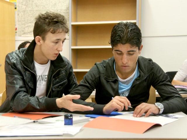 Zwei Jungs an einem Schultisch, einer schreibt und der andere gestikuliert. Im Hintergrund schreibt eine Schülerin.