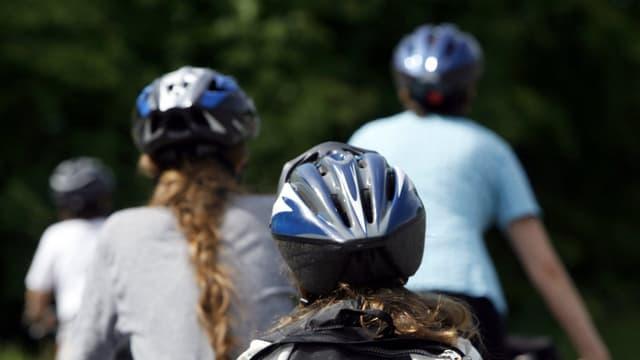 Velofahrer mit Helm von hinten aufgenommen.