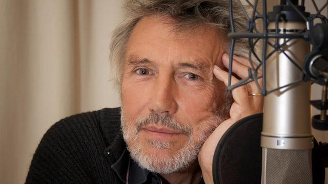 Christian Brückner mit grauem Bart und Hand am Kopf sitzt vor einem Mikrofon.