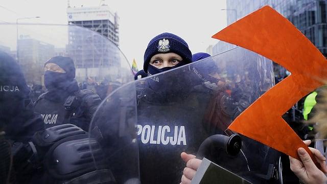 Eine Abtreibungsrecht-Demonstrantin hält das Protest-Emblem einer Polizistin in Kampfmontur entgegen.
