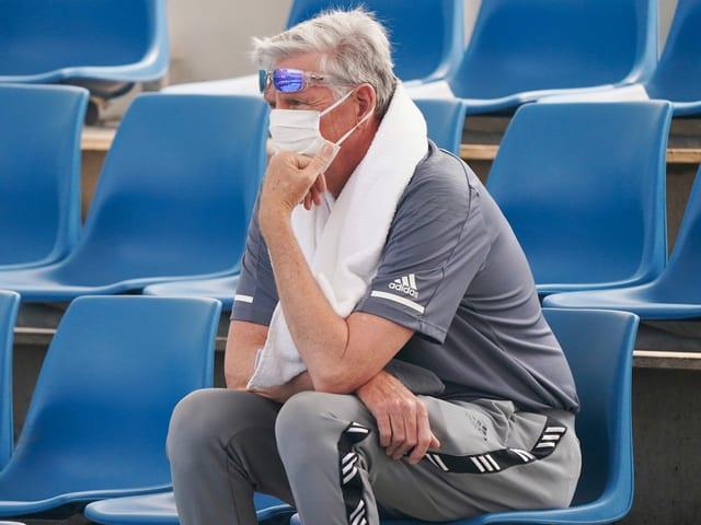 Ein Trainer trägt auf der Tribüne eine Schutzmaske.