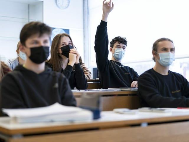 Schülerinnen und Schüler mit Maske nehmen am Unterricht teil