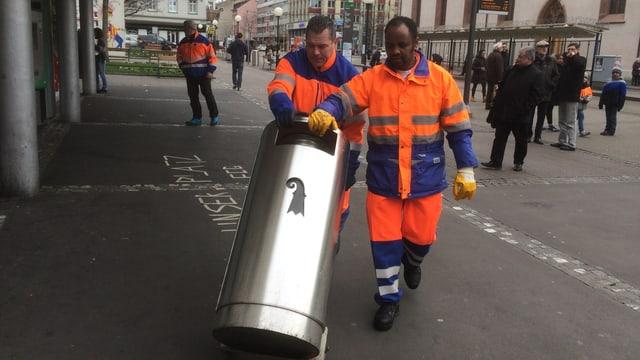 Männer transportieren einen Mülleimer.