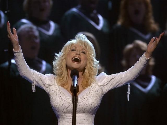 Dolly Parton streckt die Arme hoch und singt ins Mikrofon