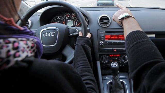 Ein Fahrlehrer zeigt einer Schülerin den Weg.