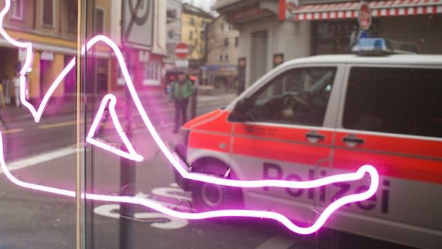 Eine Leuchtschrift und die Spiegelung eines Polizeiautos.