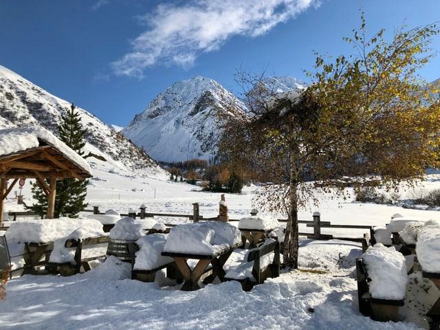 Viel Neuschnee auf Tischen und Bänken, der an der Herbstsonne langsam schmilzt.