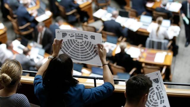 Besucherin schaut von Tribüne auf Nationalräte und auf Blatt mit Sitzordnung