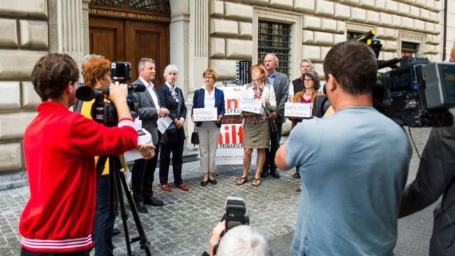 Menschen mit Kartonkisten vor Luzerner Regierungsgebäude