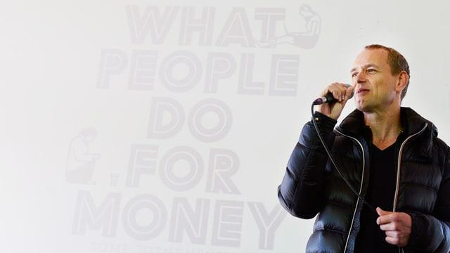 Vor dem publizierten Titel steht Christian Jankowski in einer Daunenjacke, in ein Mikrofon sprechend.
