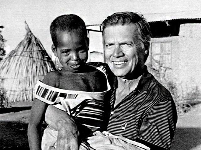 Karlheinz Böhm hält Kind im Arm.