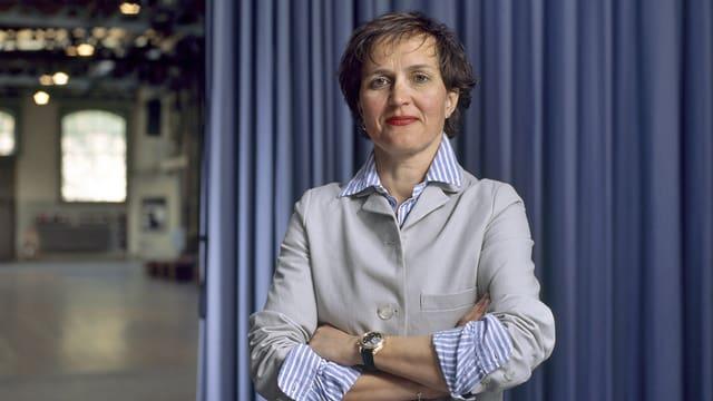 Die Intendantin des Zürcher Schauspielhauses, Barbara Frey, vor einem blauen Vorhang im Schiffbau.