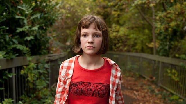 Ein Mädchen in rot-weiss kariertem Hemd und braunem Haar steht auf einer Brücke im Wald.