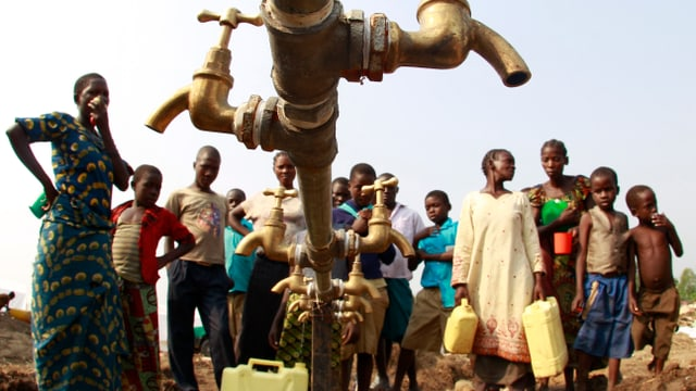 Symbolbild: Menschen – offensichtlich im ländlichen Afrika – stehen um einen Wasserhahn herum.