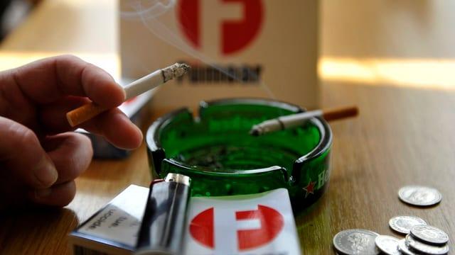 Aschenbecher mit Zigaretten im Hintergrund Fümaor-Logo
