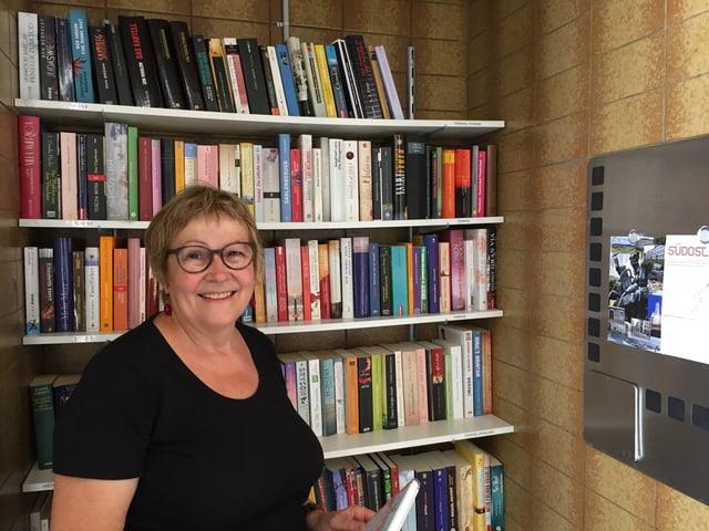 Die Verantwortliche der Mini-Bibliothek im Linsebühlquartier, Ruth Lauper, steht vor den Bücherregalen.