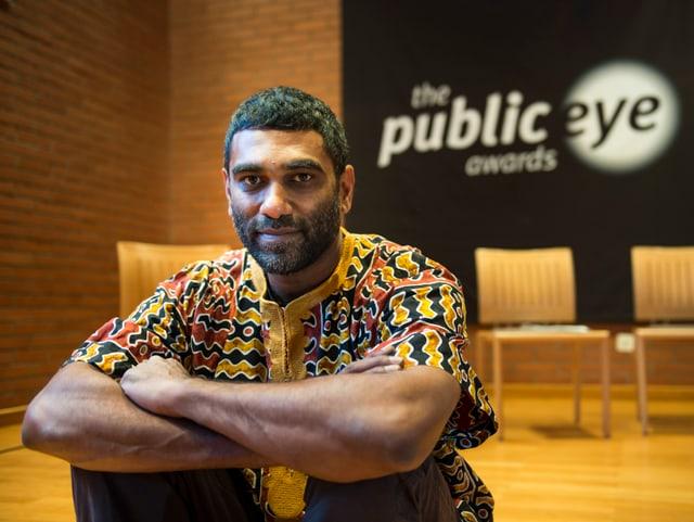Kumi Naidoo, Direktor von Greenpeace International, sitzt neben dem Logo des «Public Eye Award».
