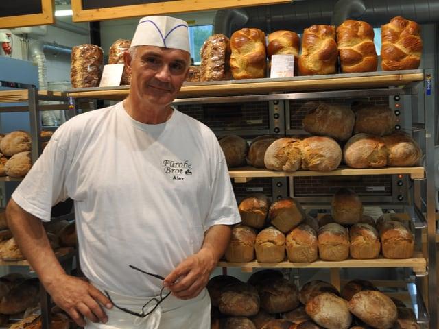 Ein Mann in weisser Kleidung steht vor einem Gestell mit Brot.