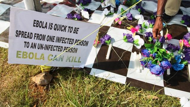 Schild mit derm Hinweis, dass Ebola töten kann und ein paar Blumen