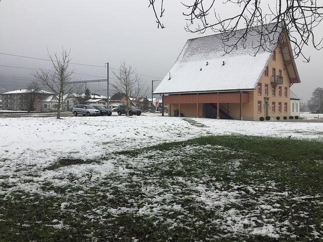 Schneebedeckte Wiese neben einem historischen Gebäude