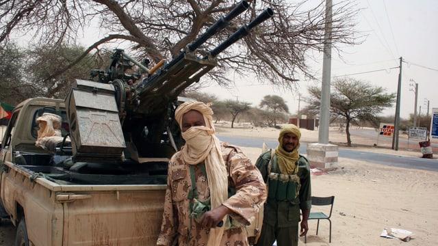 Zwei Touareg-Kämpfer vor einem Pick-Up-Wagen mit Artillerie-Geschütz