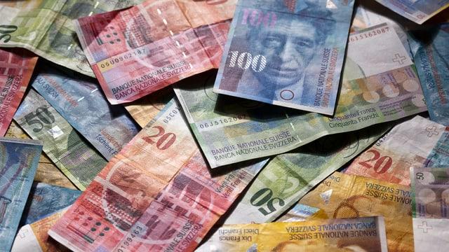 Schweizer Geldnoten liegen auf einem Tisch.