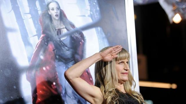 Eine Frau salutiert vor einem Filmplakat.