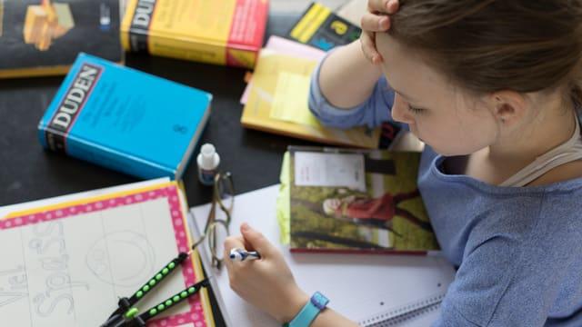 Mädchen über Bücher gebeugt, Duden, Zirkel liegen auf dem Tisch