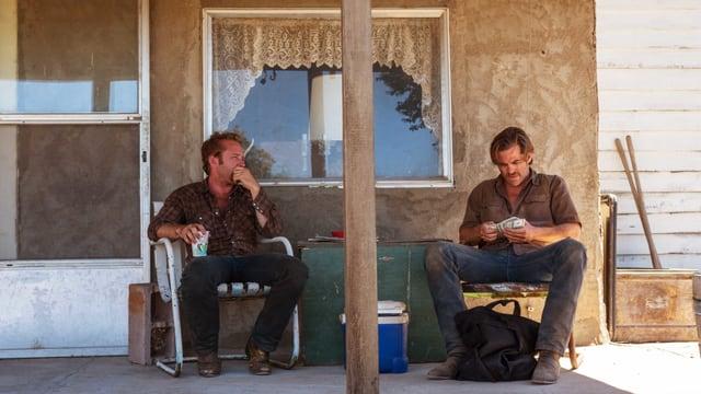 Zwei Männer sitzen vor dem Haus auf der Veranda.