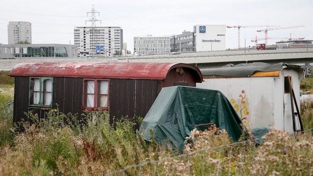 Mehrere Wohnwagen stehen auf einer Grasfläche neben einer Autobahnbrücke und Überbauungen