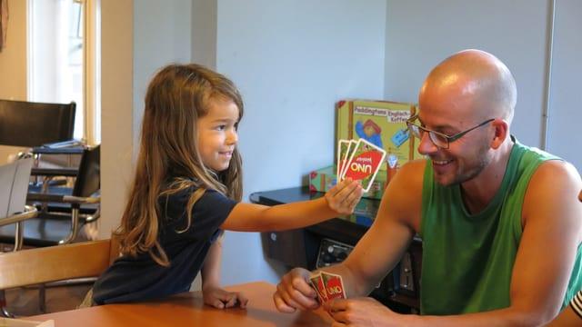 Kleiner Junge spielt Uno mit Lernbegleiter Gregor Engel