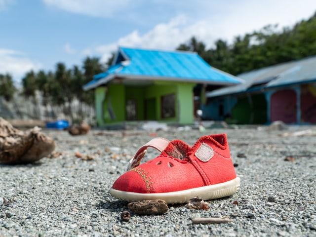 Roter Kinderschuh am Boden