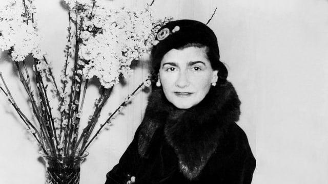 Frau mit Hut neben einem Blumenstrauss.