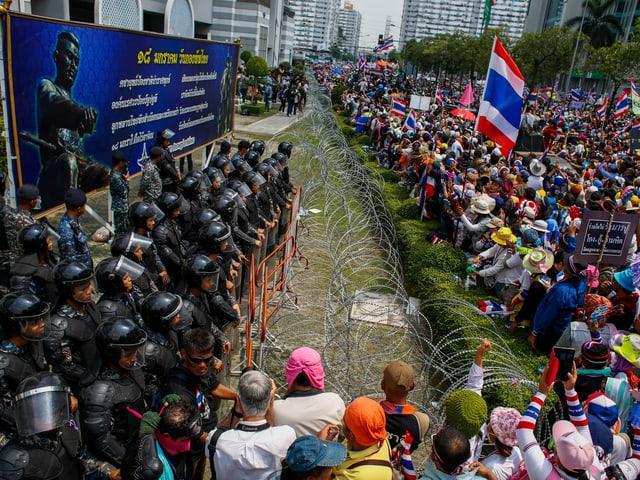 Polizisten stehen Demonstranten gegenüber. Ein Zaun trennt sie.